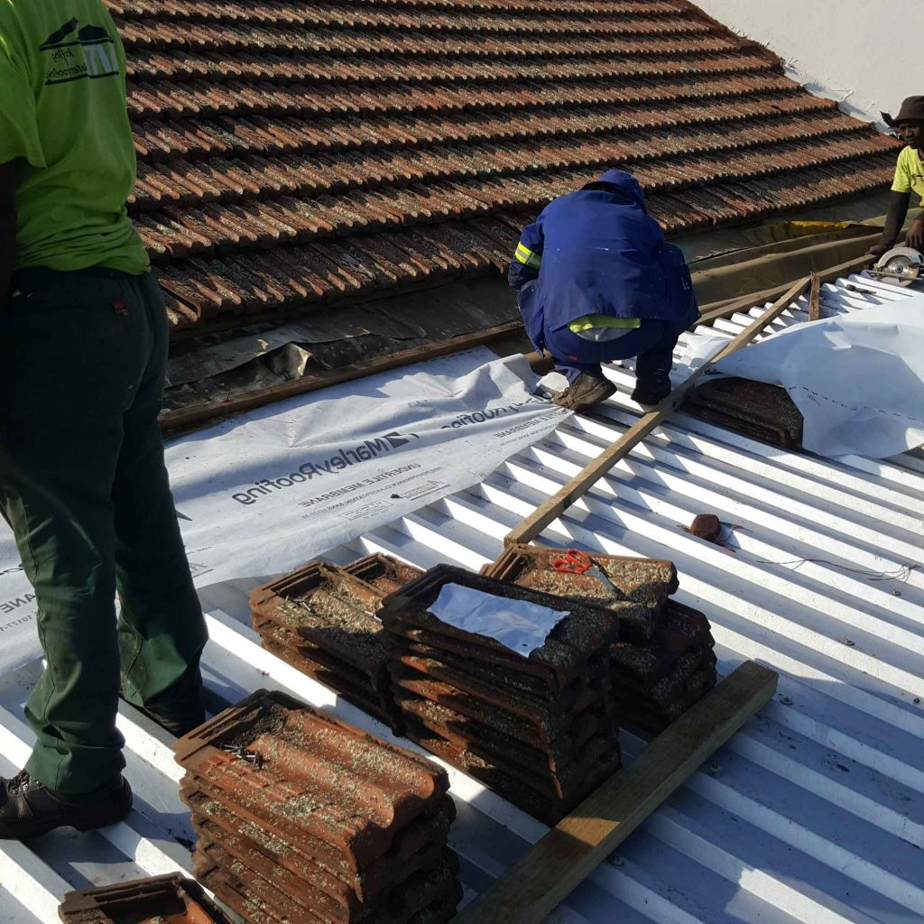 Roofing staff replacing tiles on roof